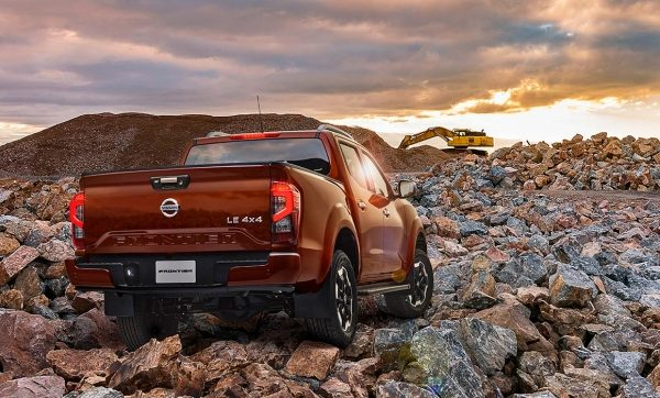 2021 Nissan Frontier showing person loading a trailer behind the vehicle