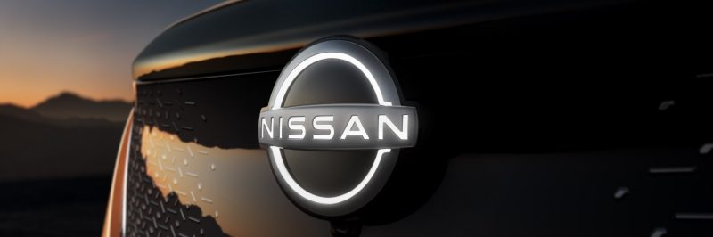 Image of an illuminated Nissan badge on the front of an Ariya