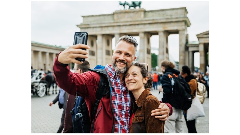 A Couple Takes A Selfie Together In Front Of Brandenburg Gate in Berlin