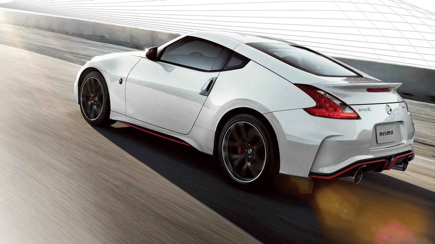 Nissan 370Z COUPÉ WHITE PEARL BRILLIANT - Vista posteriore di 7/8 in movimento sulla strada