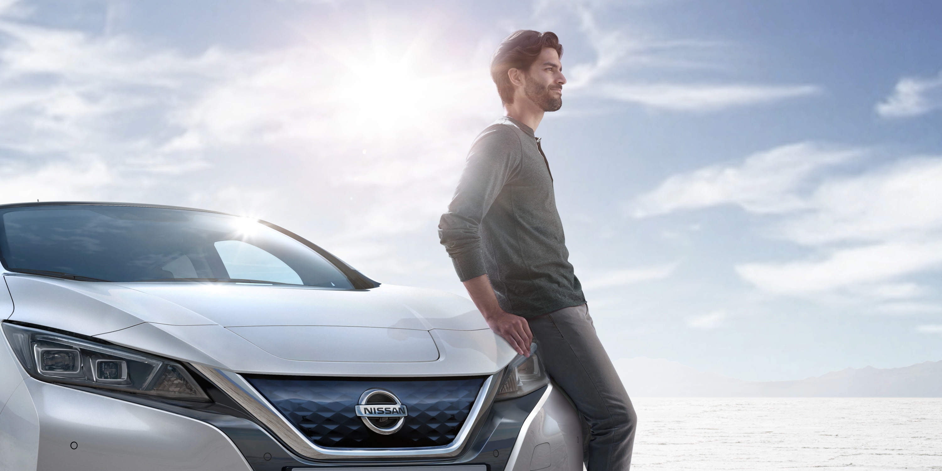 Nissan LEAF in the desert with a man leaning up against the front of the vehicle