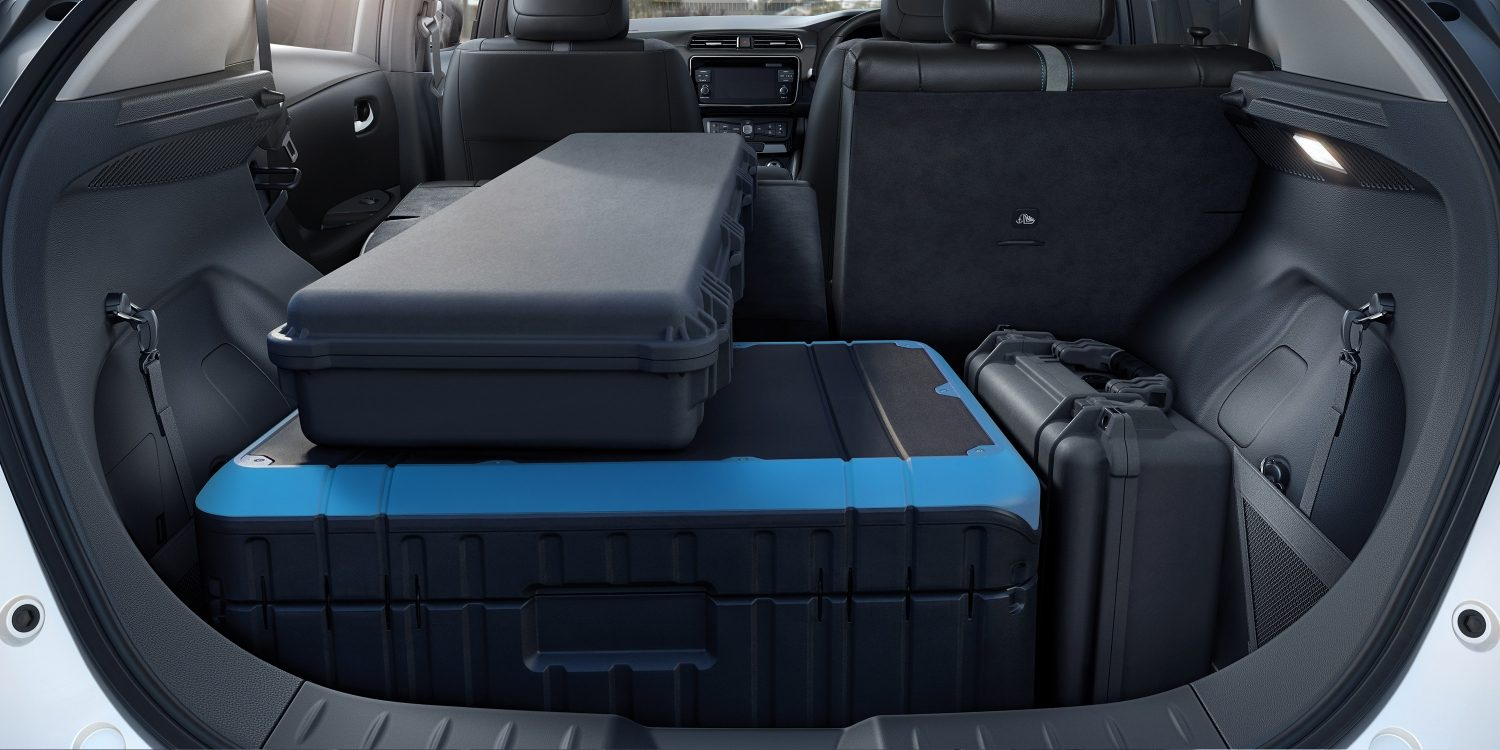 New Nissan LEAF interior showing one seat folded down and luggage in trunk