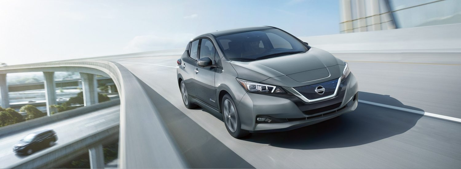 Nissan LEAF shown from the front driving on a highway overpass
