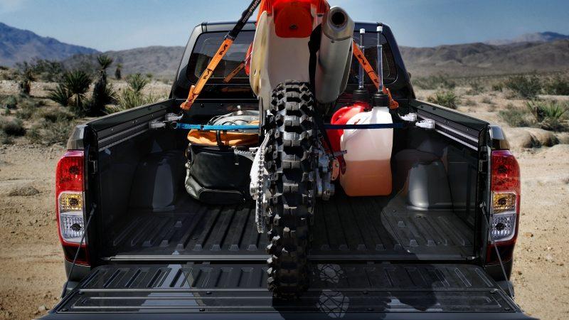 Vista estática trasera de caja con carga, con una bicicleta sucia, cargada en el desierto