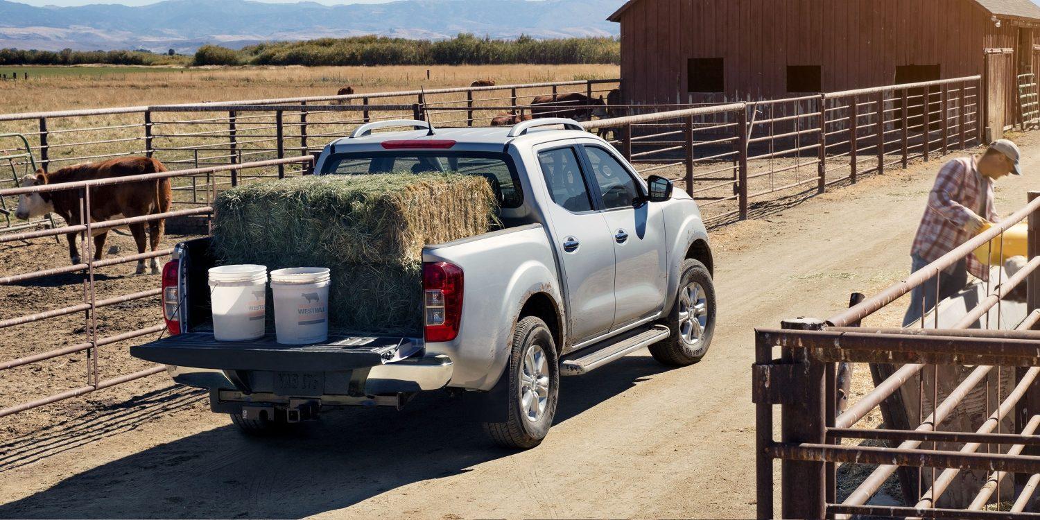 Nissan Navara parked on farm with cargo bed filled with hay
