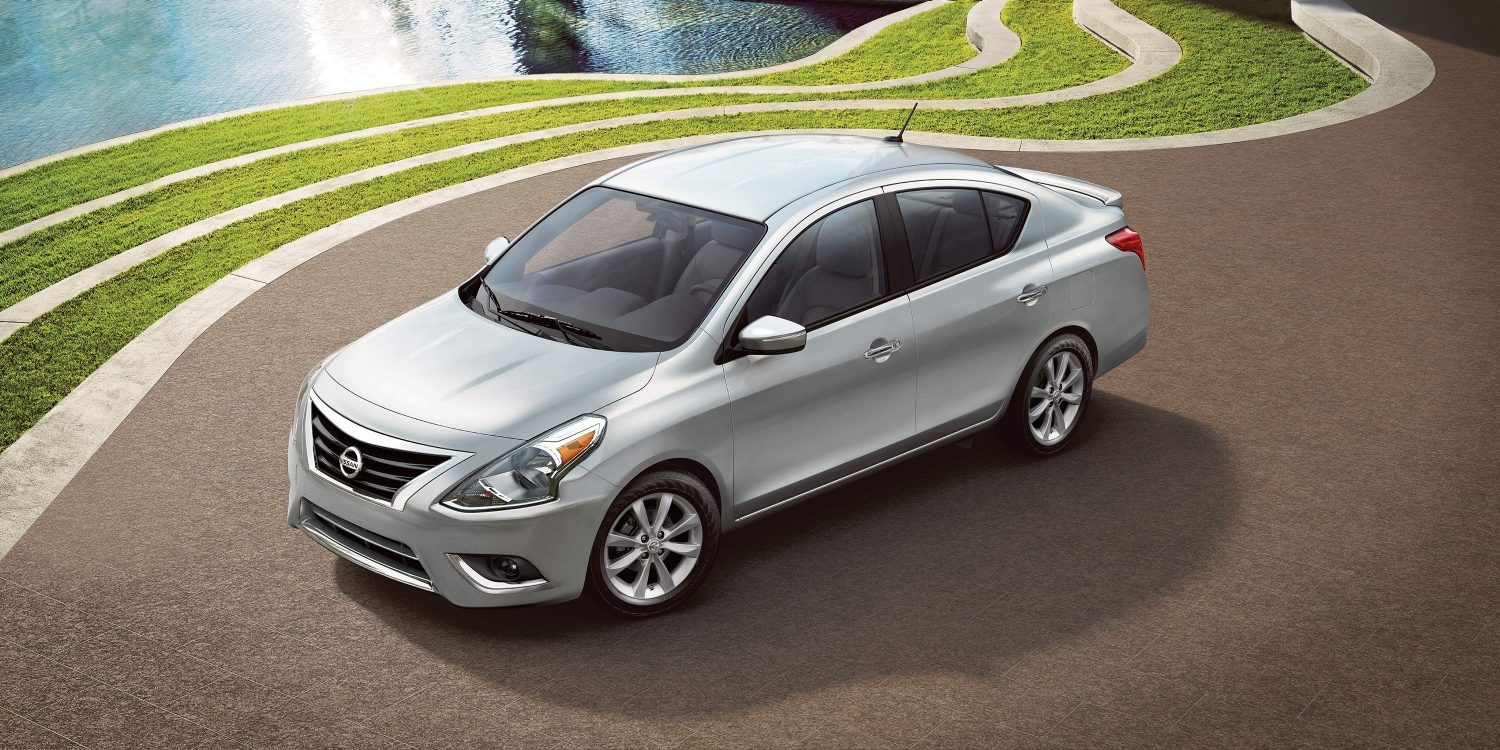 Nissan Versa parked near grass and water