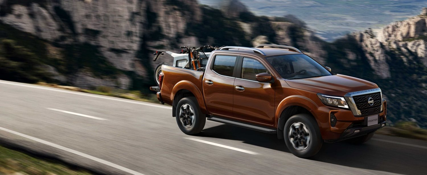 2021 Nissan Frontier on road with 2 off-road motorcycles in the back